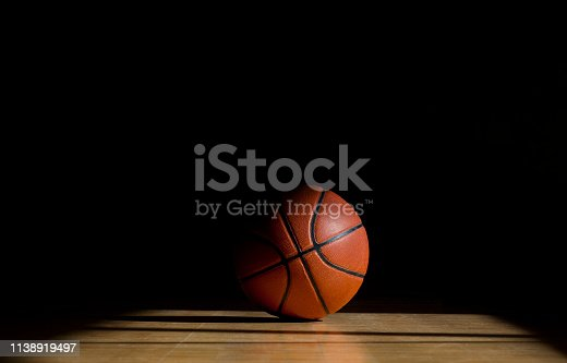 istock Basketball ball on the parquet with black background 1138919497