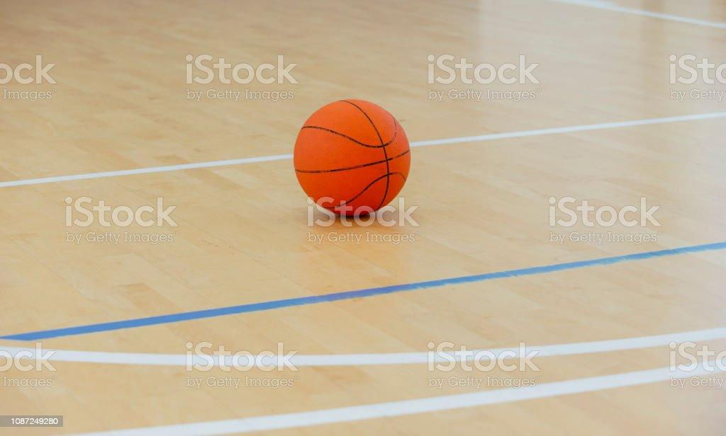Basketball ball over floor in the gym. Team sport.