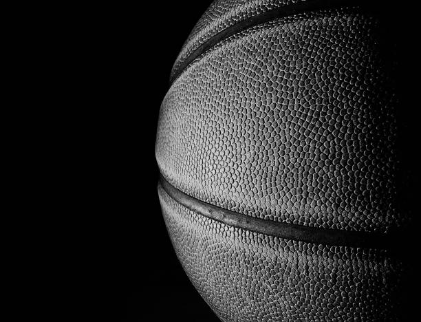 Basketball black and white closeup on black Closeup of a basketball in black and white, on black background for copy space basketball ball stock pictures, royalty-free photos & images
