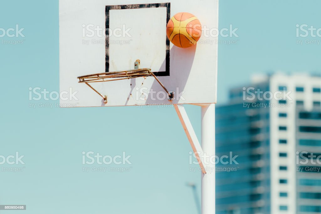 Basketball board with bouncing ball and office building in the background stock photo