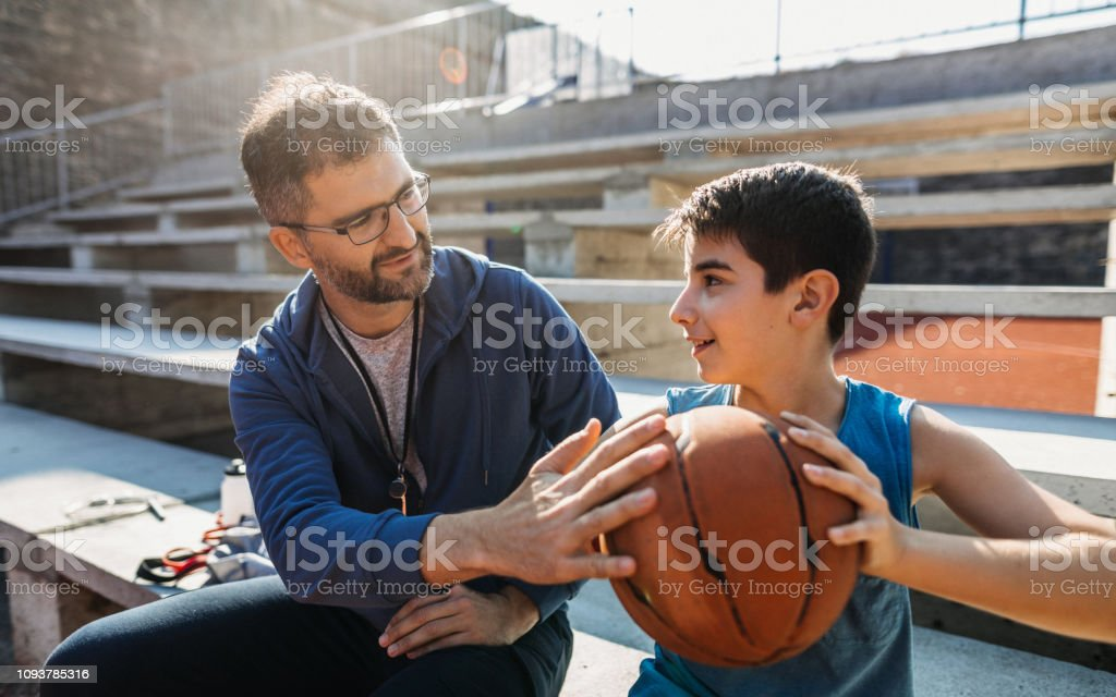 Photo of basketball coach with his young basketball player