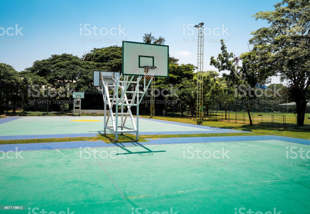 basketball court green color, day light of the sun and blue sky with...