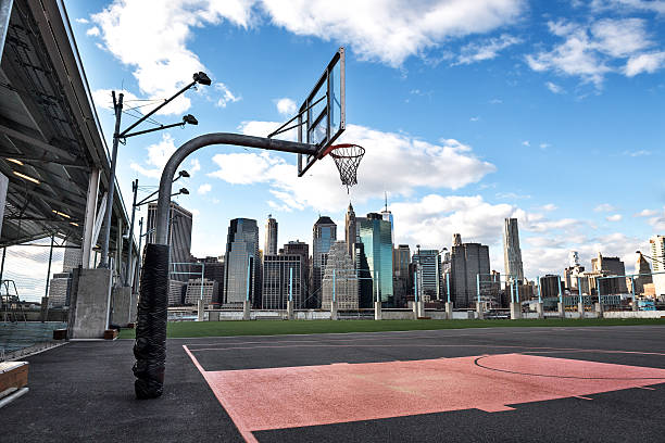 Basketball courtyard in the city New York skyscrapers are viewed behind the empty basketball courtyard. courtyard stock pictures, royalty-free photos & images