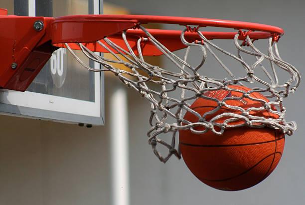 A basketball dropping through a net stock photo