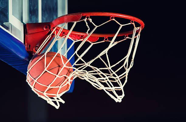 Basketball entering the hoop. stock photo