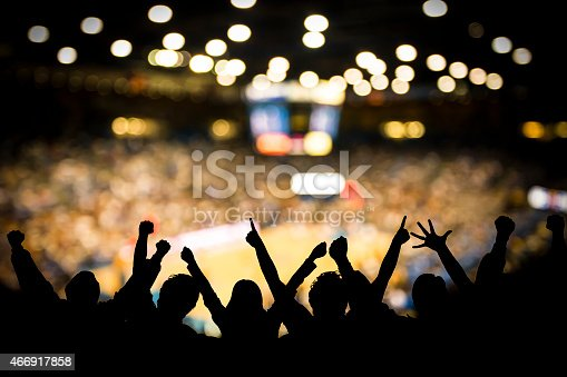 Fans excited at basketball game. Silhouetted fans raising arms in celebration at a basketball game.