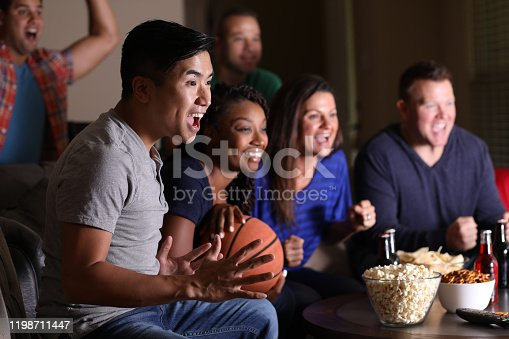 Multi-ethnic group of basketball fans watching the game together on television at home.  They have snacks, drinks, and sports ball.  Asian descent man foreground.