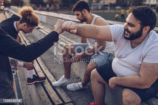 Group of men, street basketball friends sitting on bleachers on a sunny day outdoors, taking a break.