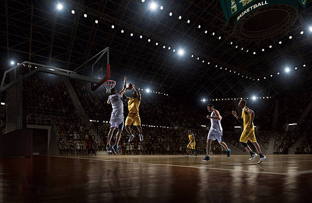 Basketball game Low angle view of a professional basketball game. A player is in mid air holding ball about to score a slam dunk, but the player from the opposite team is ready to block him.  A  game is in a indoor floodlit basketball arena. All players are wearing generic unbranded basketball uniform. basketball ball stock pictures, royalty-free photos & images