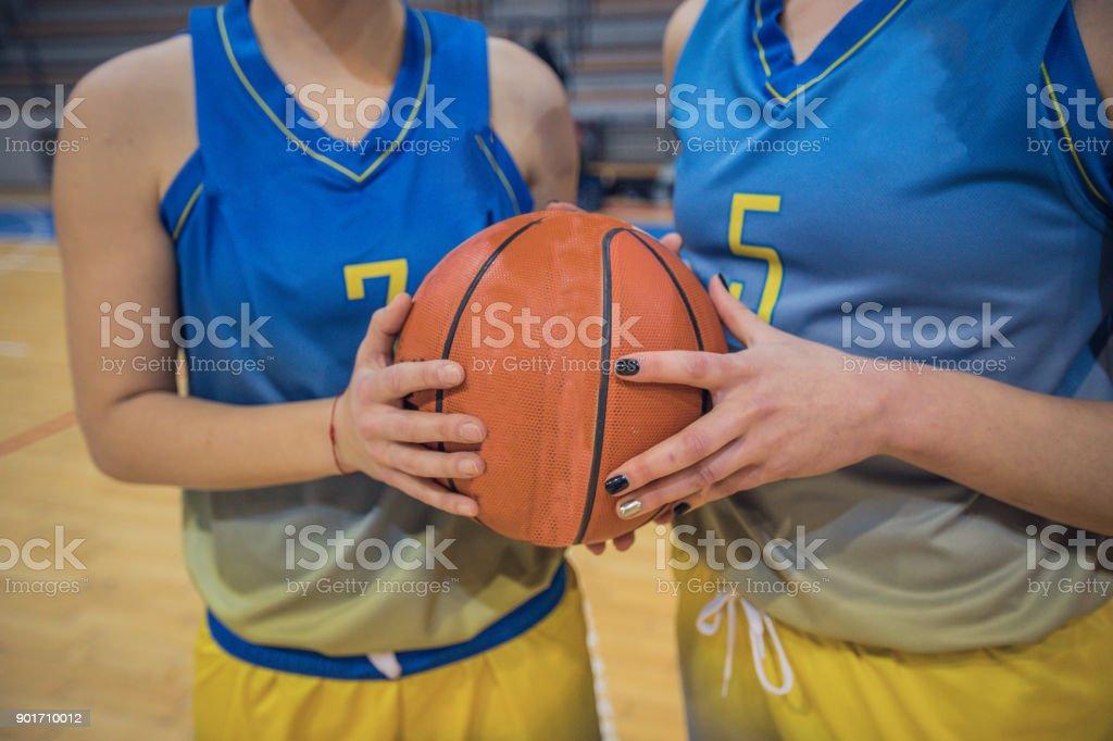 Two female basketball players holding basketball ball