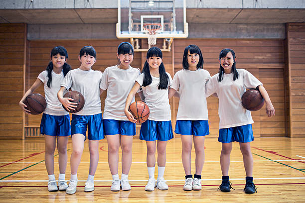 Basketball girls team in the school gymnasium Portrait of a Japanese basketball girls team in the school gymnasium. japanese school girl stock pictures, royalty-free photos & images