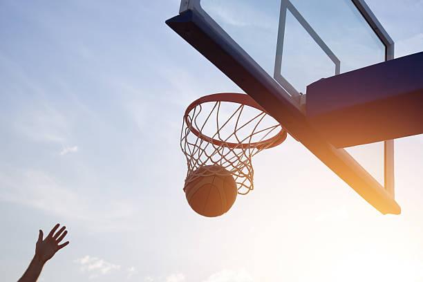 Basketball going through the basket stock photo