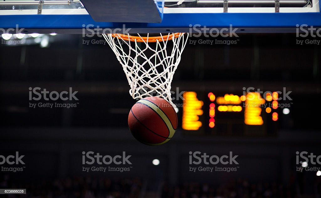 Basketball going through the hoop at a sports arena stock photo