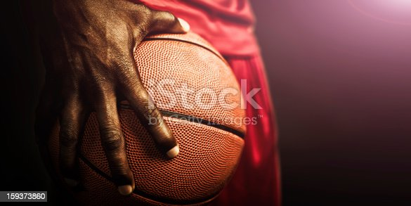 Hand tightly gripping basketball up close.