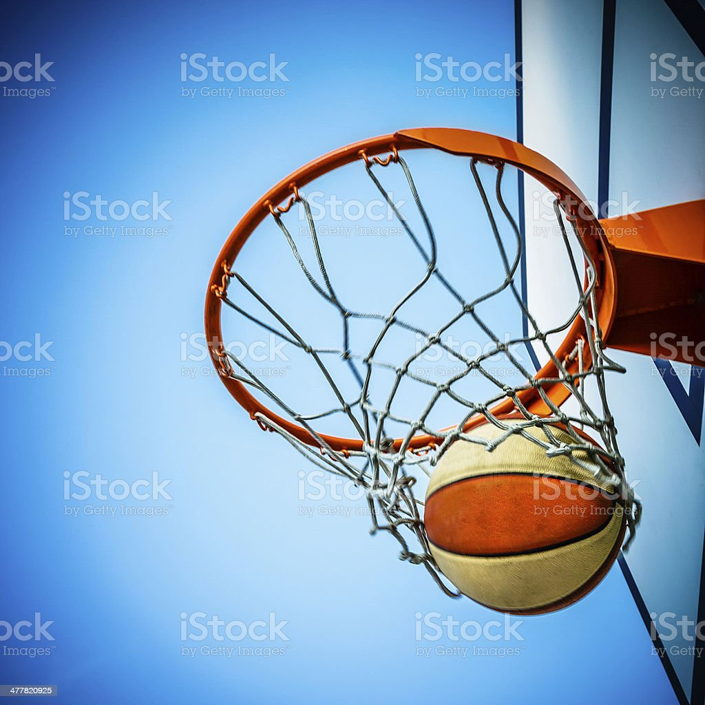 Basketball hitting in hoop with net stock photo