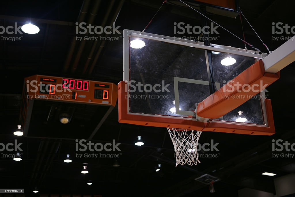 A basketball hoop and a scoreboard above that  stock photo