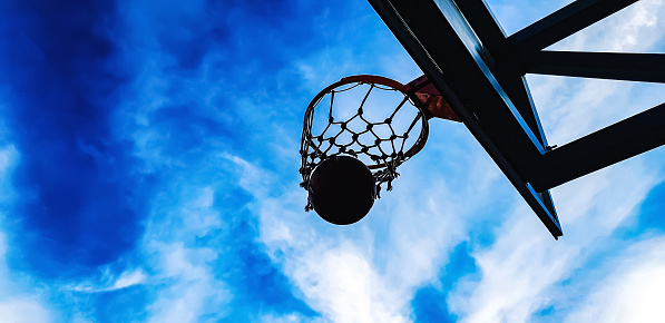 istock basketball hoop and ball on the sky background 1038682714