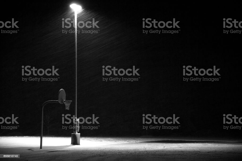 Basketball hoop at night in the snow-Horizontal. stock photo