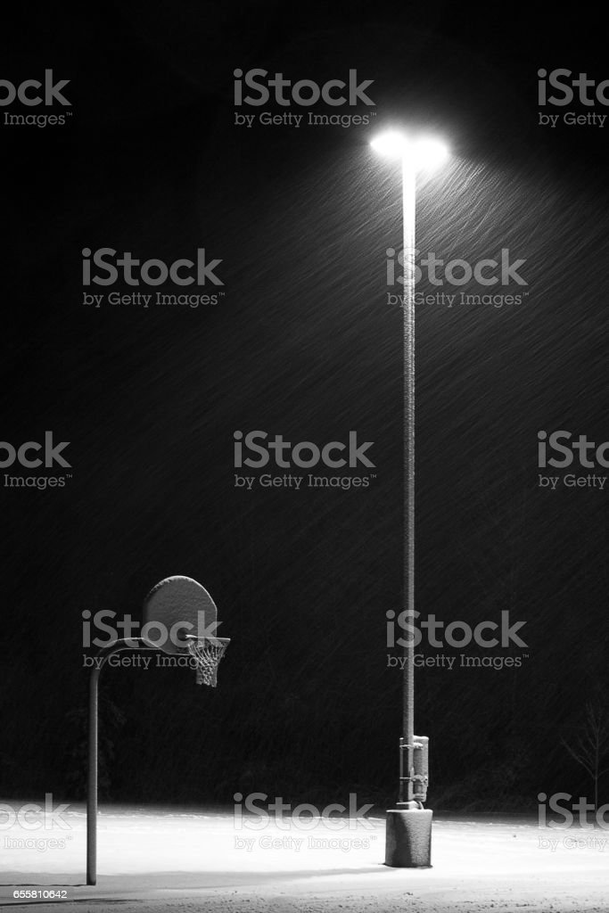 Basketball hoop at night in the snow-Vertical. stock photo