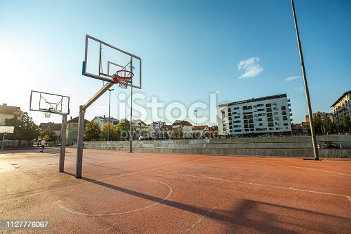 Basketball hoop on sport field in the hood, on sunny summer day