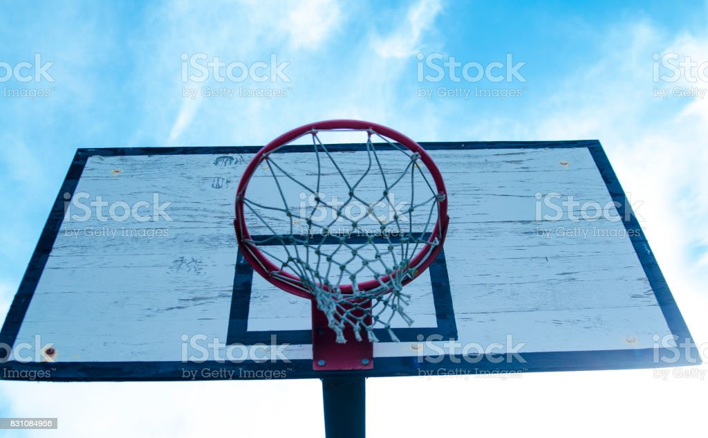 Basketball hoop outdoor photo from bellow. Blue sky background with copy paste. stock photo