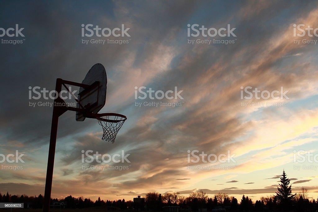 basketball hoop silhoutte at dusk - cloudy sky stock photo