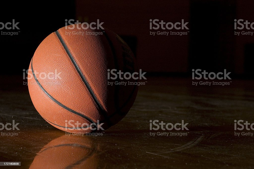 A basketball in a dark gym. Ball on left of image.