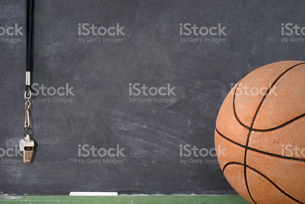 A basketball in front of a chalkboard and hanging whistle stock photo