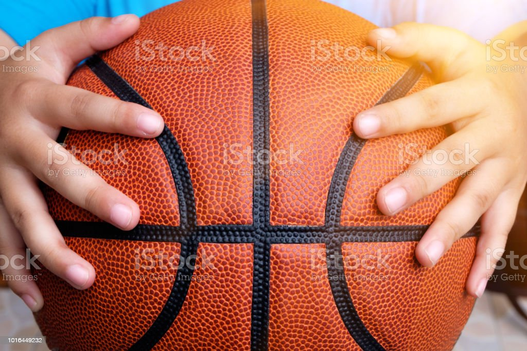 Basketball in the hands of children. stock photo