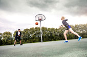 Basketball man-woman playing in a London playground, UK.