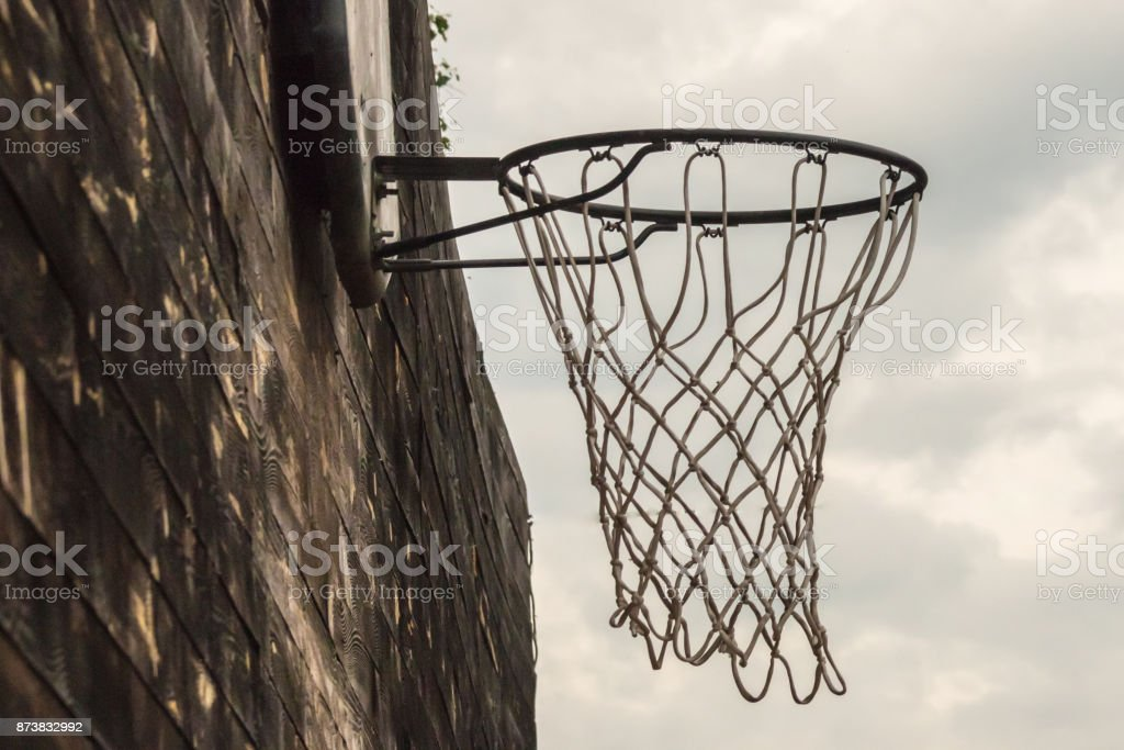 Basketball net on a street wooden wall on a sky background close stock photo