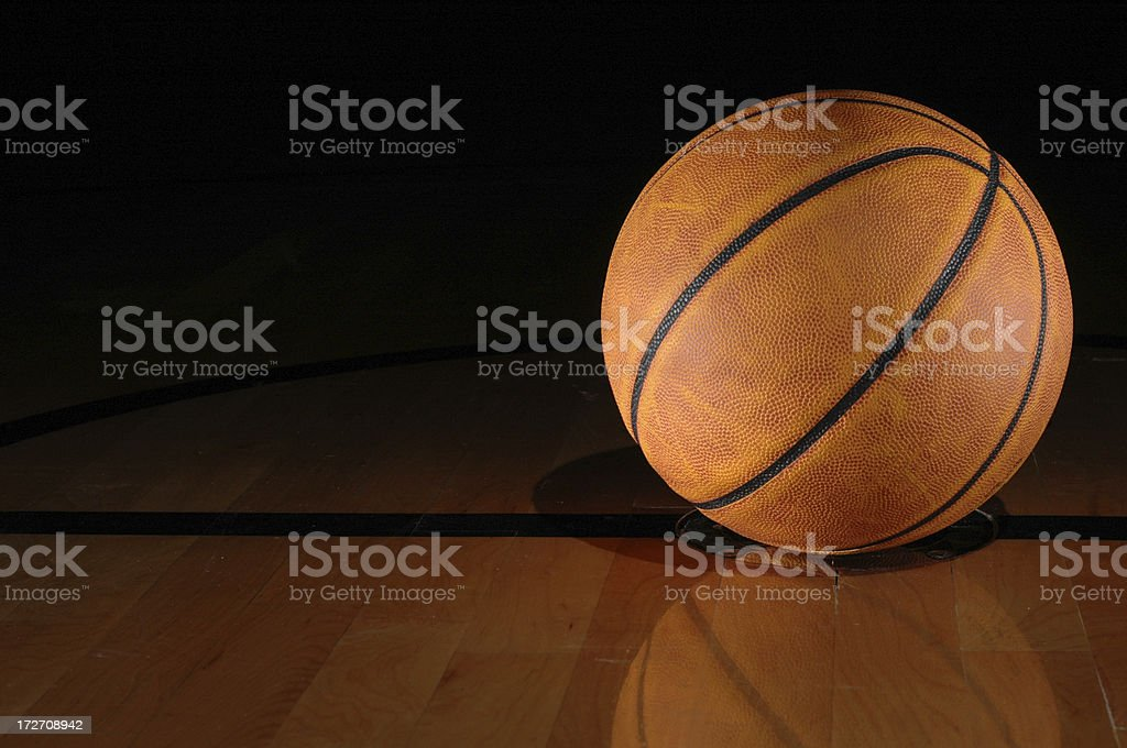 A basketball sits on a gymnasium floor. The ball is positioned in the...