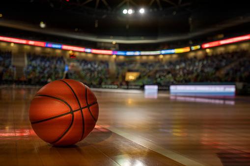 Basketball on court in stadium.