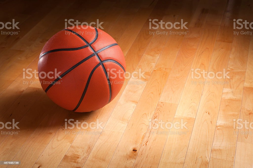 An orange basketball sits on a hardwood court floor with spot...