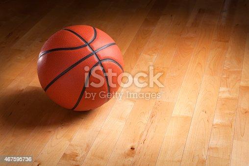 istock Basketball on hardwood court floor with spot lighting 467595736