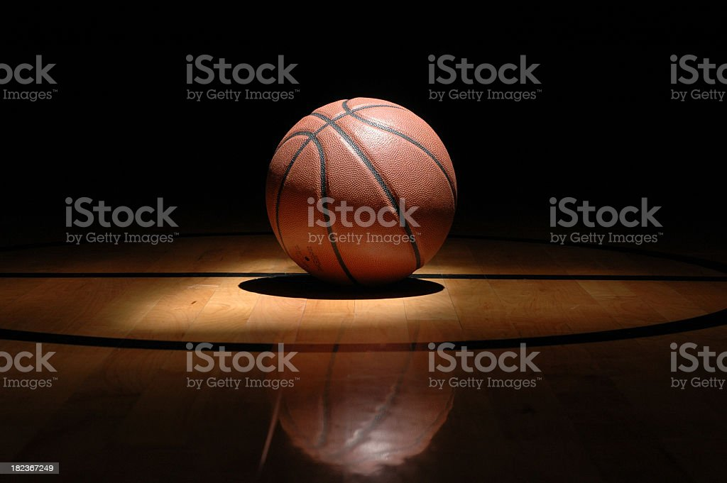 Basketball on middle of court with spotlight shows game time royalty-free stock photo