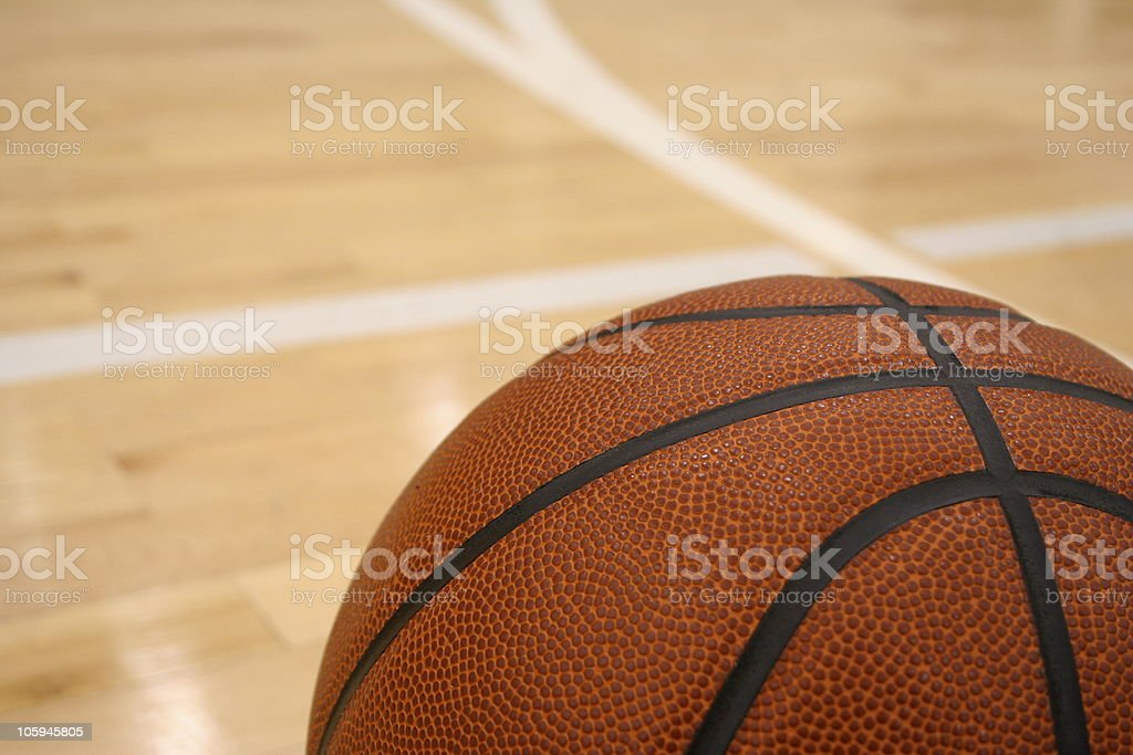 Basketball on the Hardwood of an Indoor Court stock photo