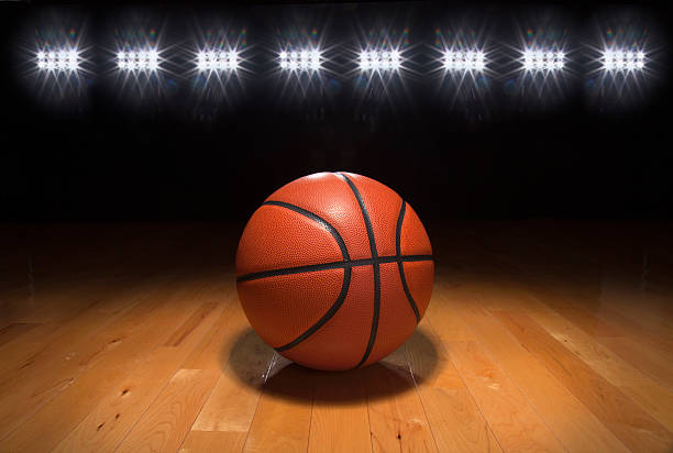 Basketball on wood floor beneath bright lights stock photo