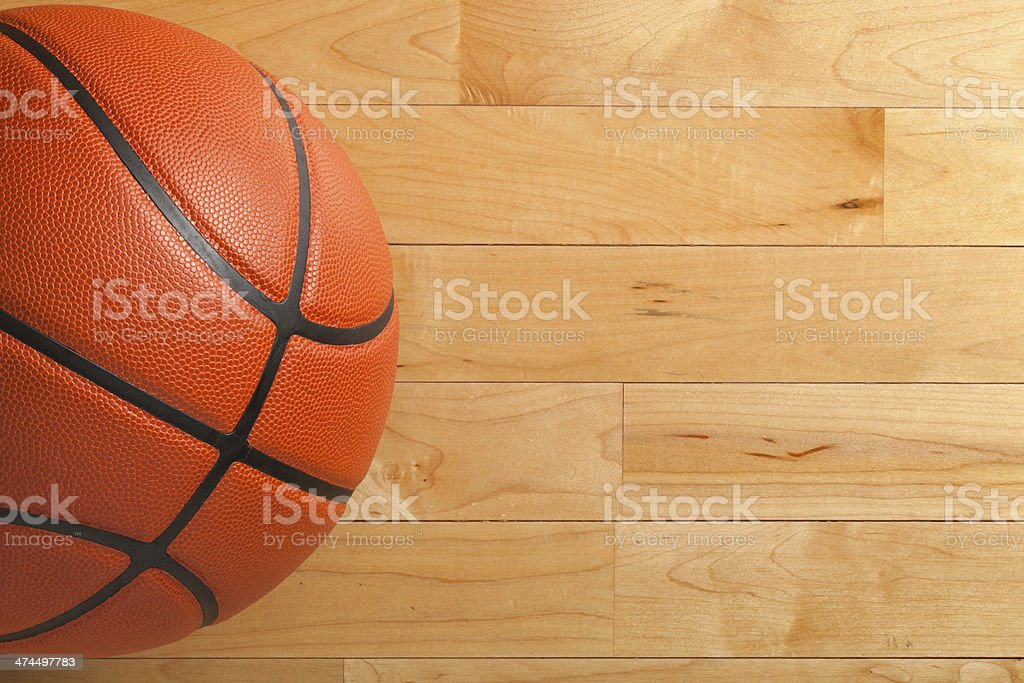 Basketball on wood gym floor viewed from above stock photo