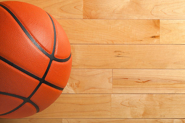 basketball on wood gym floor viewed from above - basketball ball stock photos and pictures