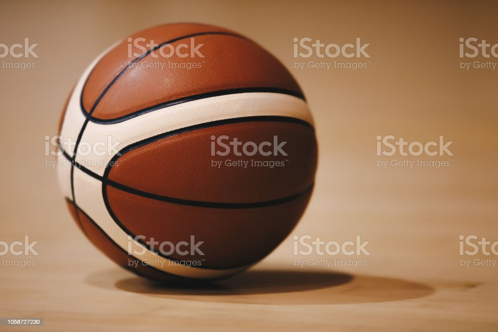 Basketball on Wooden Court Floor Close Up with Blurred Arena in...