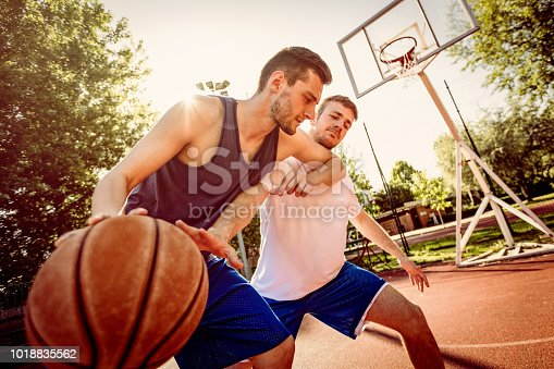 Two street basketball players playing one on one. They are making a good action and guarding the ball.