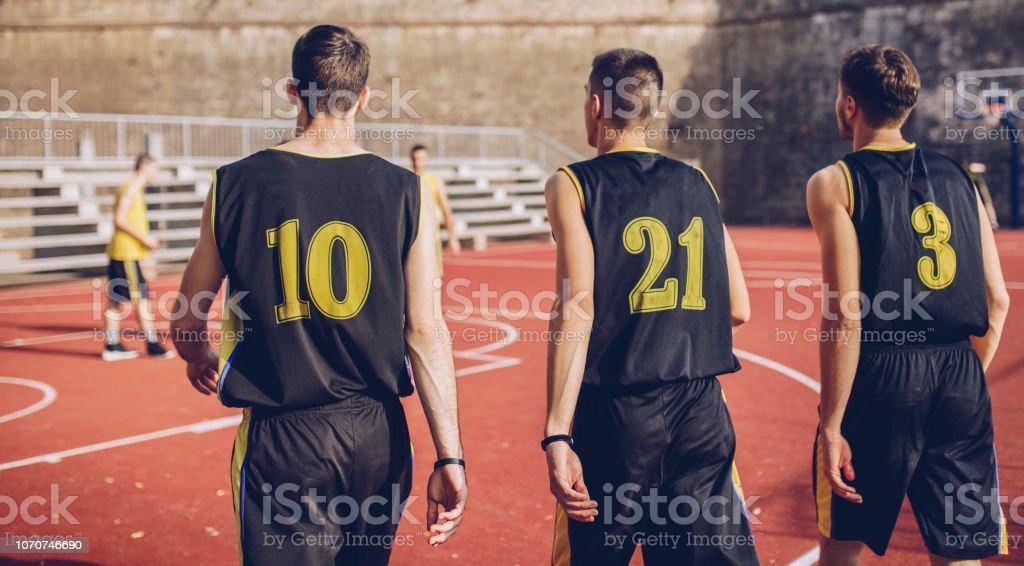 Group of male basketball players playing basketball