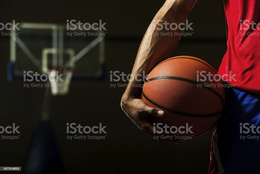 Unrecognizable basketball player holding basketball.