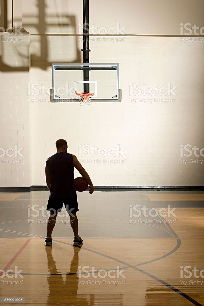 Basketball player alone in basketball court stock photo