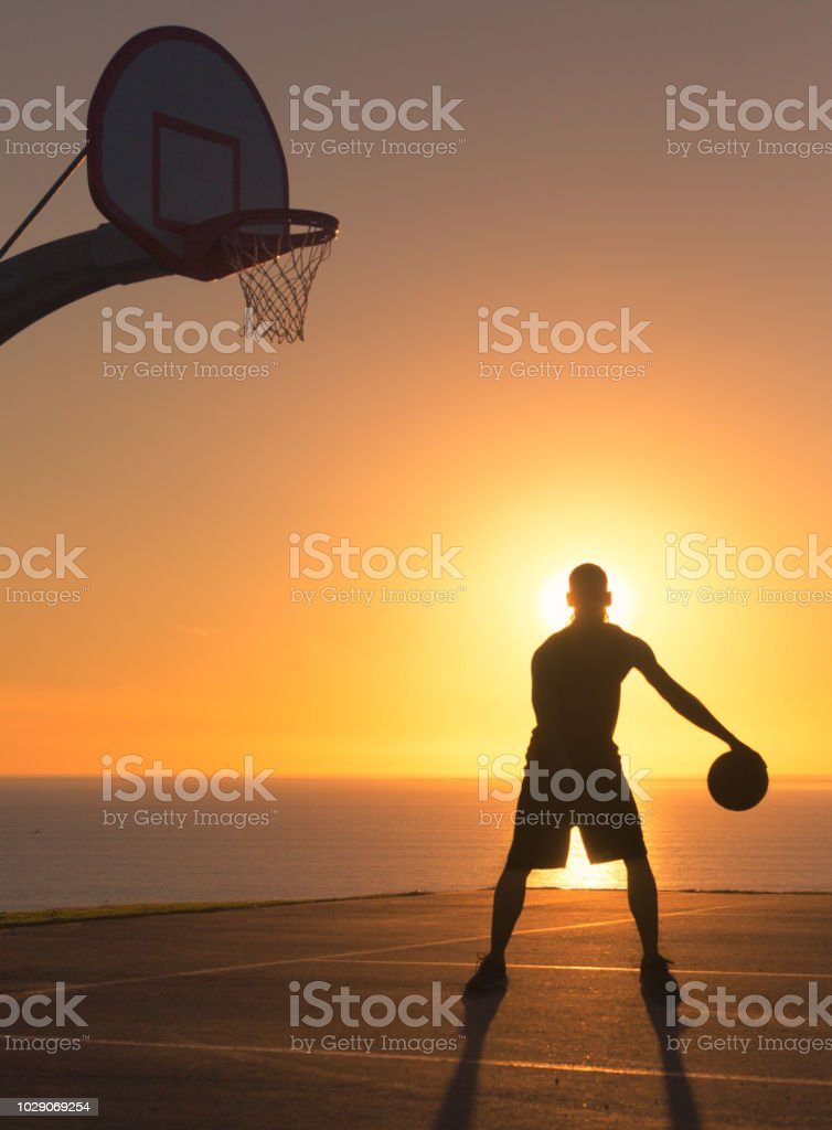 Basketball player dribbling a ball at sunset. Silhouette stock photo