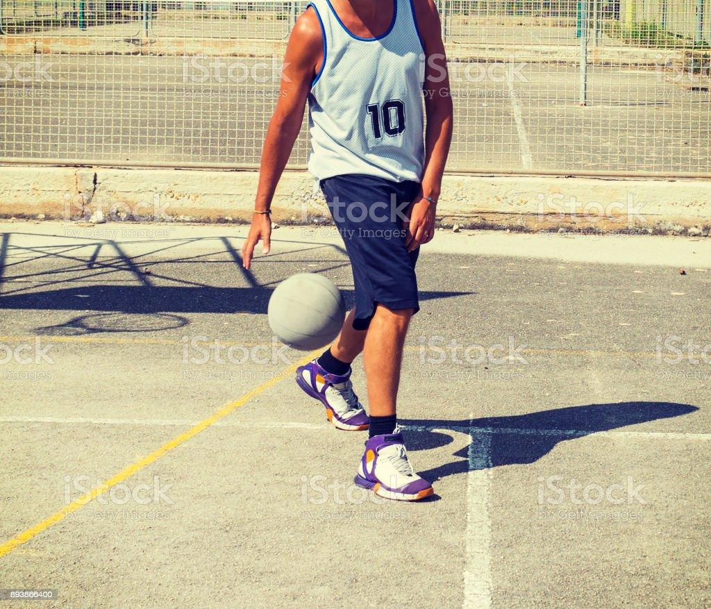 Basketball player dribbling betweeen the legs stock photo