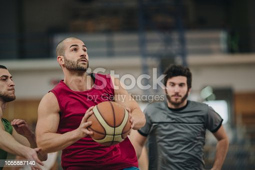 Determined athlete trying to pass his opponents on a basketball match.
