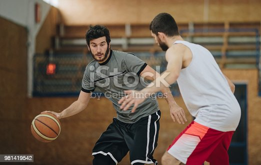 Athletic man dribbling his opponent during basketball match.