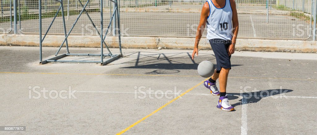 Basketball player dribbling in a playground stock photo
